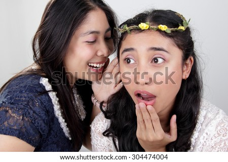 Two beautiful Asian girls gossiping. One girl with surprised face expression while her friend says something on her ear, over grey background - stock photo