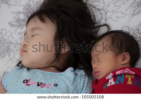 Two Beautiful Asian Sister Toddler and Baby Sleeping together soundly