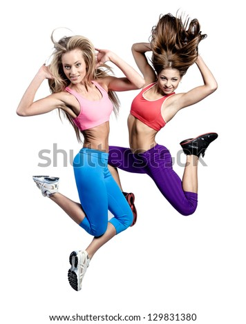 Two beautiful athletic girl jumping over white background - stock photo