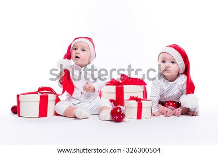 Two beautiful baby in the New Year's cap and white body sitting among festive boxes with gifts and Christmas balls, picture with depth of field - stock photo