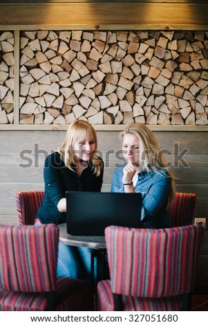 Two beautiful blond girls working on the laptop in coffee bar.