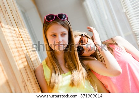 Two beautiful blond teenage girls having fun happy smiling - stock photo