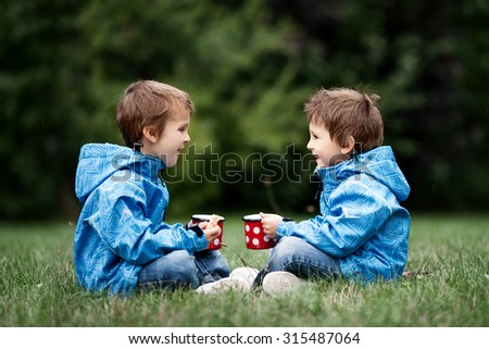 Two beautiful boys, brothers, sitting on a lawn, autumn time, drinking tea and eating cookies in the park - stock photo
