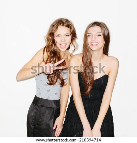 Two beautiful brunette girls having fun. Wearing dresses. Makeup and long curly hair. Inside - stock photo