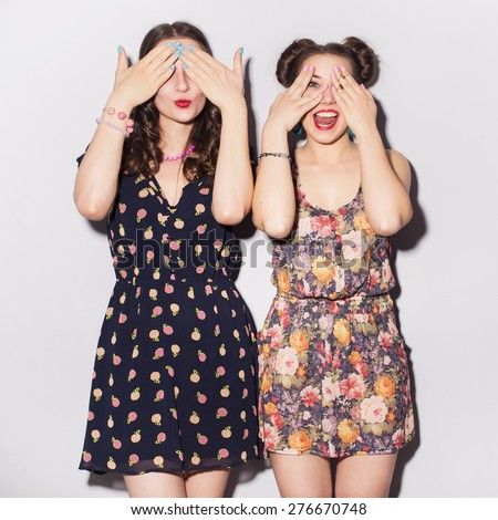 Two beautiful brunette women (girls) teenagers spend time together having fun, make funny faces. Casual hipsters outfit: romantic dresses - stock photo