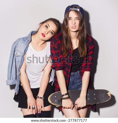 Two beautiful brunette women (girls) teenagers spend time together having fun, make funny faces. Casual hipster outfit, jeans jacket and plaid shirt, with a skateboard