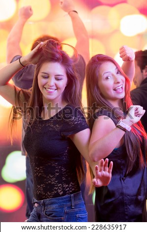 two beautiful brunette young fun girls dancing in a club