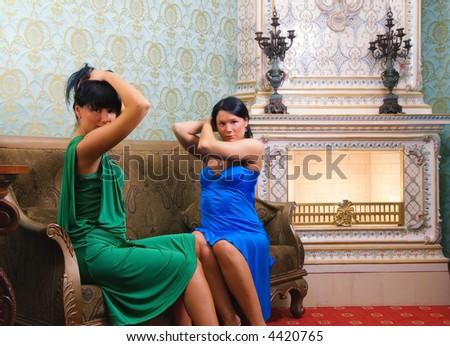 Two beautiful brunettes sitting on a sofa near the luxury fireplace - stock photo