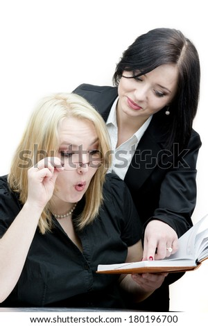Two beautiful business woman sharing ideas with each other.   Shot in the studio on an isolated white background. - stock photo