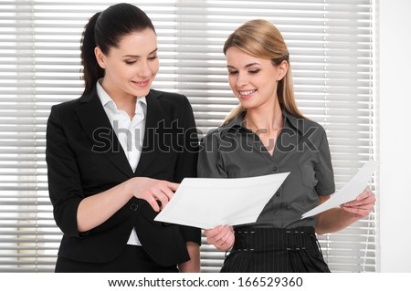 Two beautiful business woman sharing ideas with each other. Standing together and checking documents in modern office  - stock photo