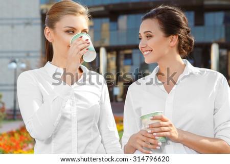 Two beautiful businesswoman having a coffeebreak outdoors - stock photo