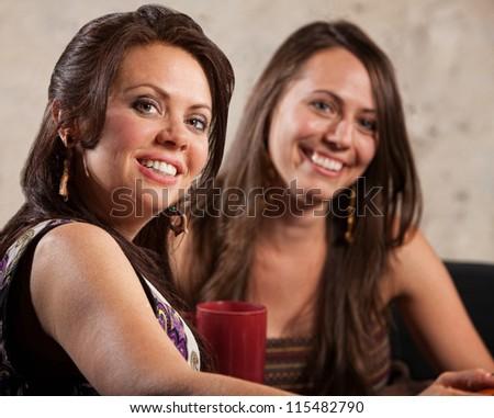 Two beautiful Caucasian brunette females sitting indoors - stock photo