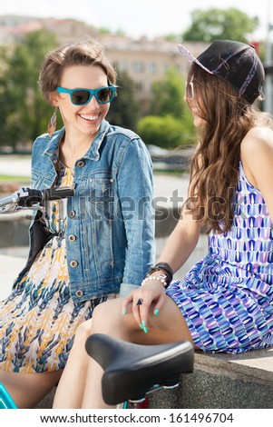 two beautiful chatting  girls in sunglasses with a bike in the city - stock photo