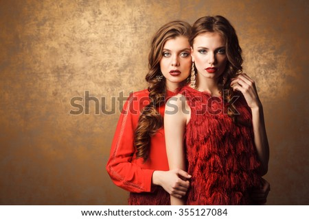 Two beautiful cheerful women in red dress. Stock photo.