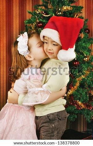 two beautiful child stand near christmas tree - stock photo