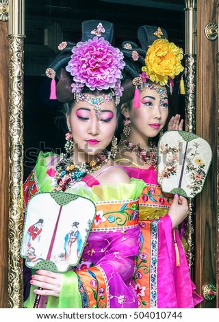 two beautiful Chinese girl in traditional Chinese dress out of the door