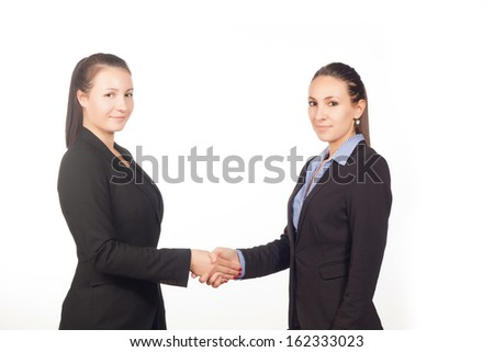 Two beautiful confident business women shaking hands isolated on white