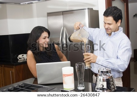 Two beautiful couple cooking in kitchen with appliances and laptop