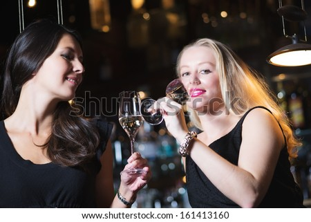 Two beautiful elegant women friends in stylish simple black cocktail dresses drinking a glass of chilled champagne as they celebrate on a night out together