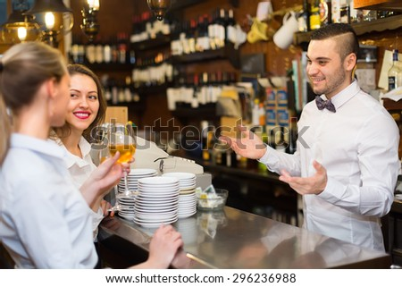 Two beautiful european girls flirting with handsome barman