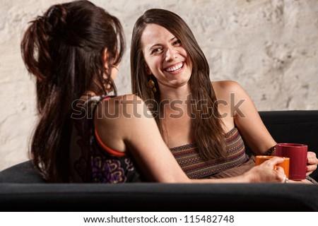 Two beautiful European ladies sitting indoors laughing - stock photo