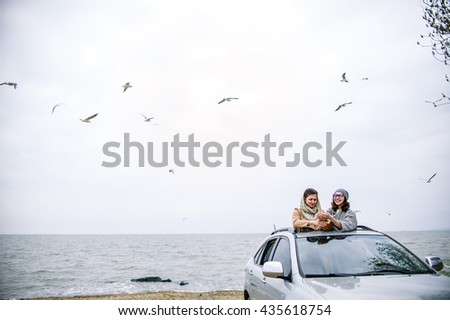 Two beautiful European women tourists leaned out of the car roof and enjoy the life against the sea and seagull