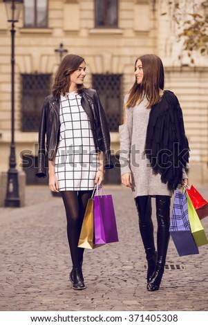 two beautiful fashion models posing outside with shopping bags; two young women laughing, having fun - stock photo