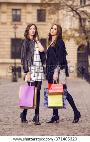 two beautiful fashion models posing outside with shopping bags; two young women walking in the city - stock photo