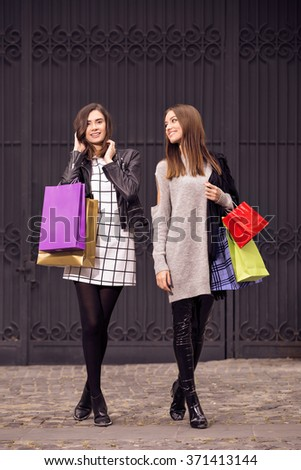 two beautiful fashion models with shopping bags, posing outside, on dark background;  two young women laughing, having fun - stock photo
