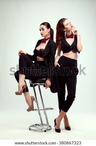 Two beautiful fashion young women in black suit with red bow-tie, posing. Studio portrait. Bar stool.