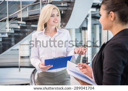 Two beautiful female business partners dressed formal discuss project at office. - stock photo
