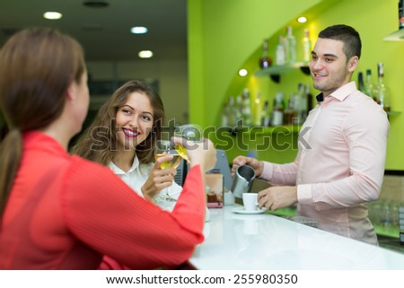 Two beautiful female friends flirting with handsome barman - stock photo