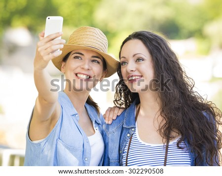 Two beautiful female friends making a selfie with cellphone - stock photo