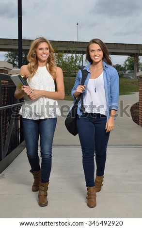 Two beautiful female students together on campus - walking holding books or backpack - stock photo