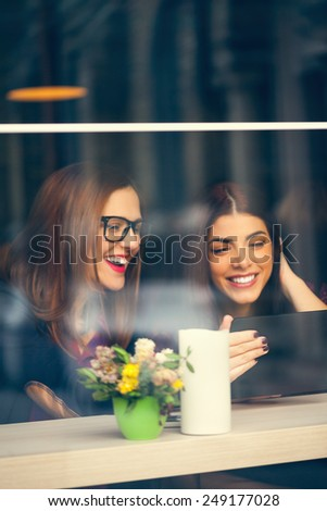 Two Beautiful Females In Cafe Using Digital Tablet - stock photo
