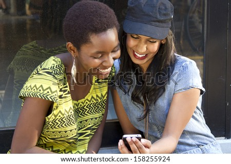 Two beautiful friends looking at a smart phone outside - stock photo