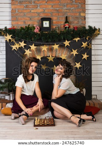 Two beautiful girl friends playing chess by the fireplace - stock photo
