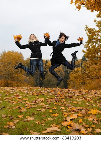 two beautiful girl friends with autumn leafs in a park jumping - stock photo