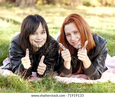 Two beautiful girlfriends at the autumn park near tree. Outdoor shot.
