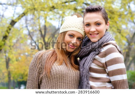 Two beautiful girlfriends having fun in the park on colorful autumn day. - stock photo