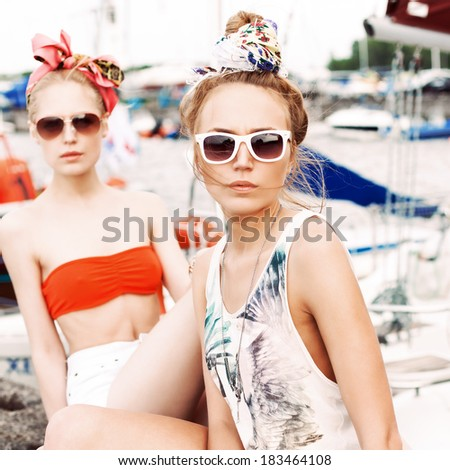 two beautiful girlfriends in fashion summer style sit against yachts looking into camera - stock photo