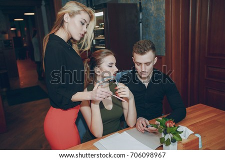Two beautiful girls and a guy in a cafe at a table doing business affairs