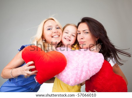 Two beautiful girls and a little girl with hearts - stock photo