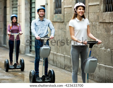 Two beautiful girls and guy traveling through city by segways