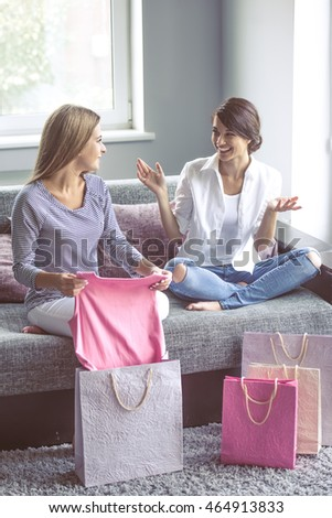 Two beautiful girls are examining their new clothes, talking and smiling while sitting on the couch at home