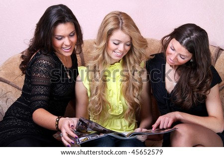 Two beautiful girls are looking magazine - stock photo