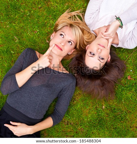 Two beautiful girls brainstorming in the grass. - stock photo