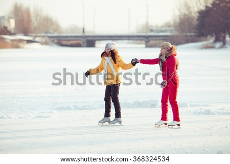 two beautiful girls ice skating outdoor on a warm winter day - stock photo