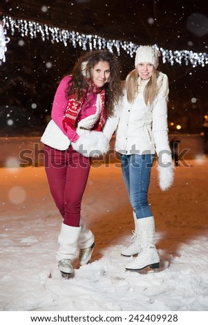 two beautiful girls ice skating outdoor on a warm winter night - stock photo