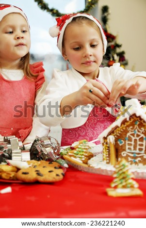 two beautiful girls in caps decorates  gingerbread house - stock photo